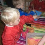 Toddlers engaged in painting at Hugo and Holly Nursery