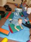 Pre school children using soft gym equipment at Hugo and Holly Nursery