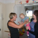 Baby being greeted by Key worker on arriving at Hugo and Holly Nursery